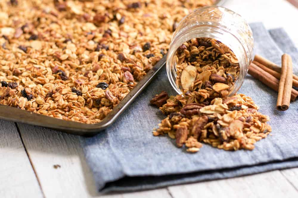 Maple Pecan Granola on baking sheet with granola filled jar pouring out.