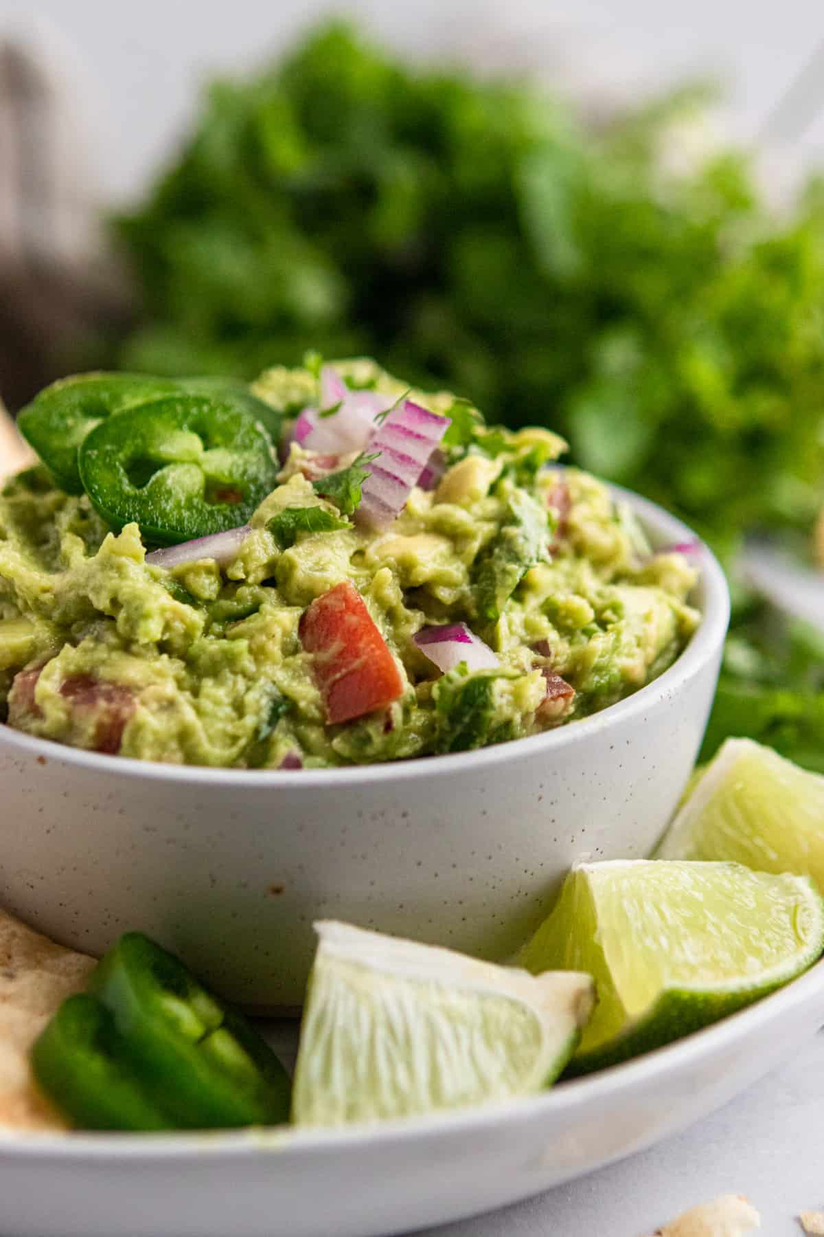 Healthy guacamole recipe on plate with limes.