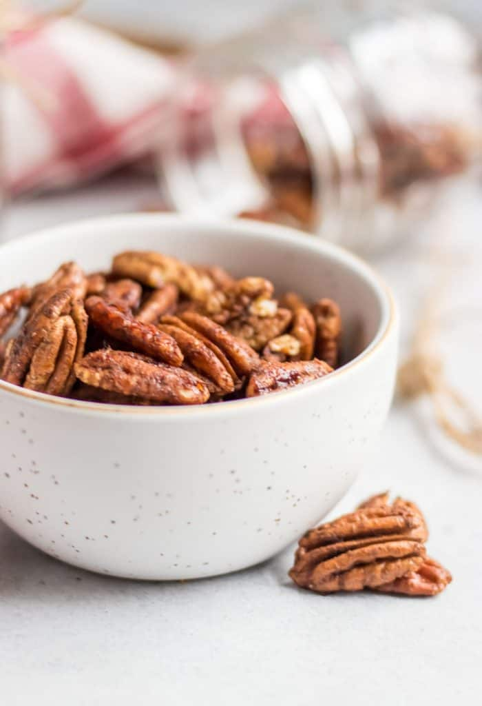 Simple roasted and maple sweetened pecans with a dusting of cinnamon and hints of vanilla are the perfect snack, holiday treat, salad topper and more! This easy spiced pecan recipe makes perfect holiday gifts as well!