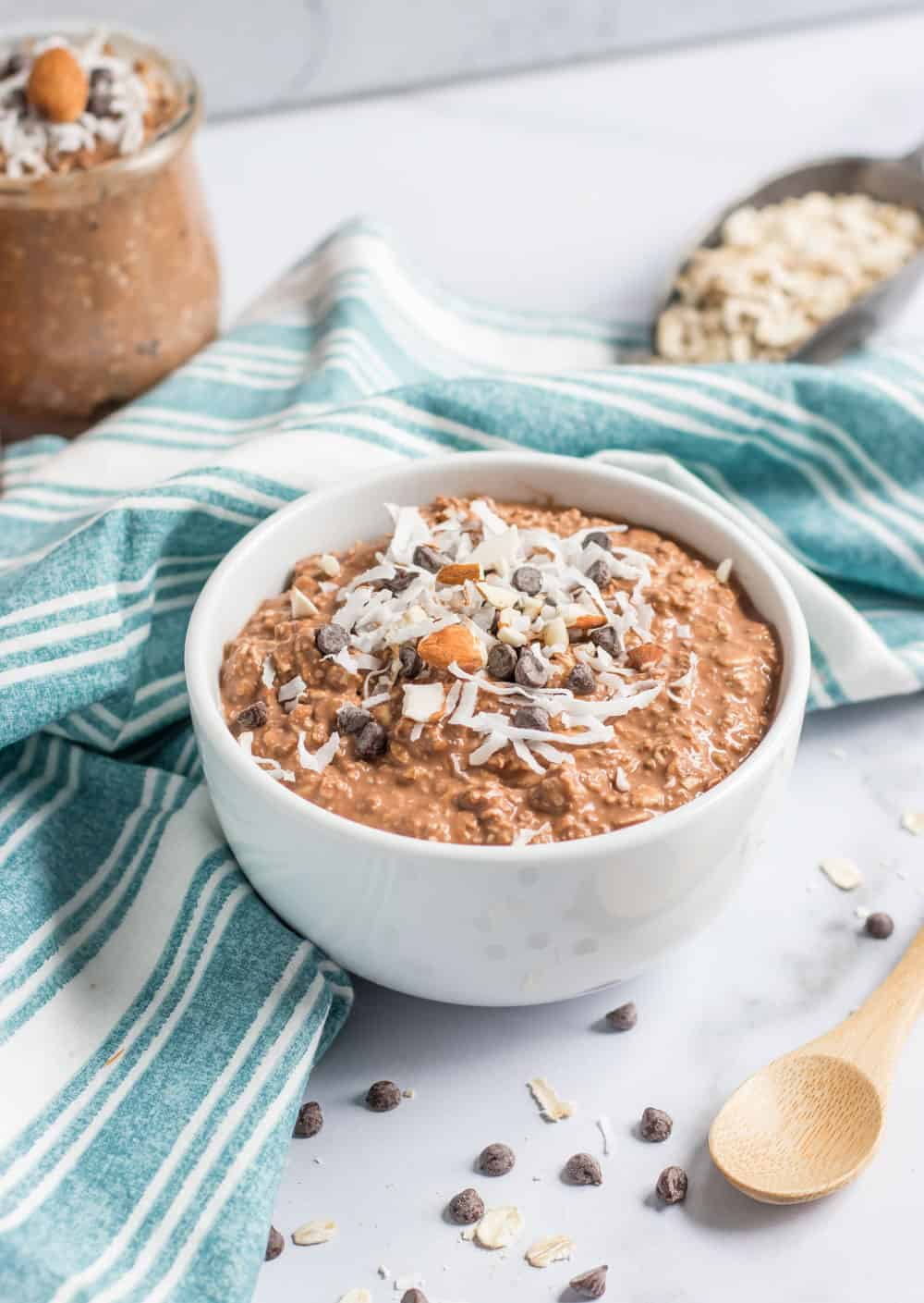 Chocolate overnight oats in white bowl with chocolate chips and coconut.
