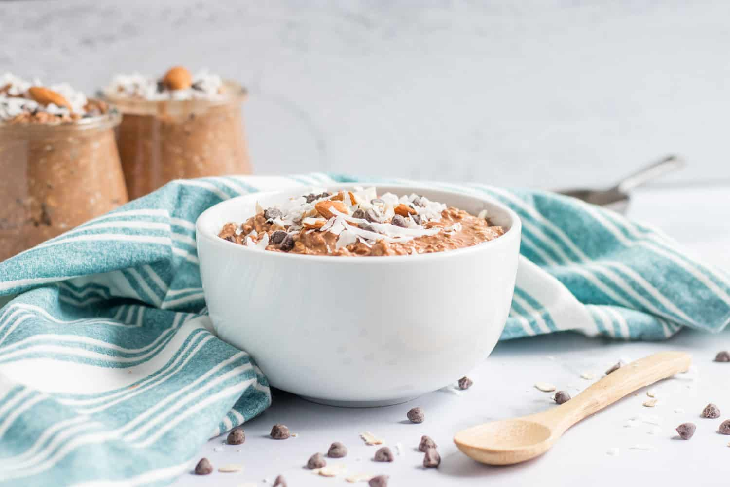 White bowl with almond joy overnight oats and jars in background.