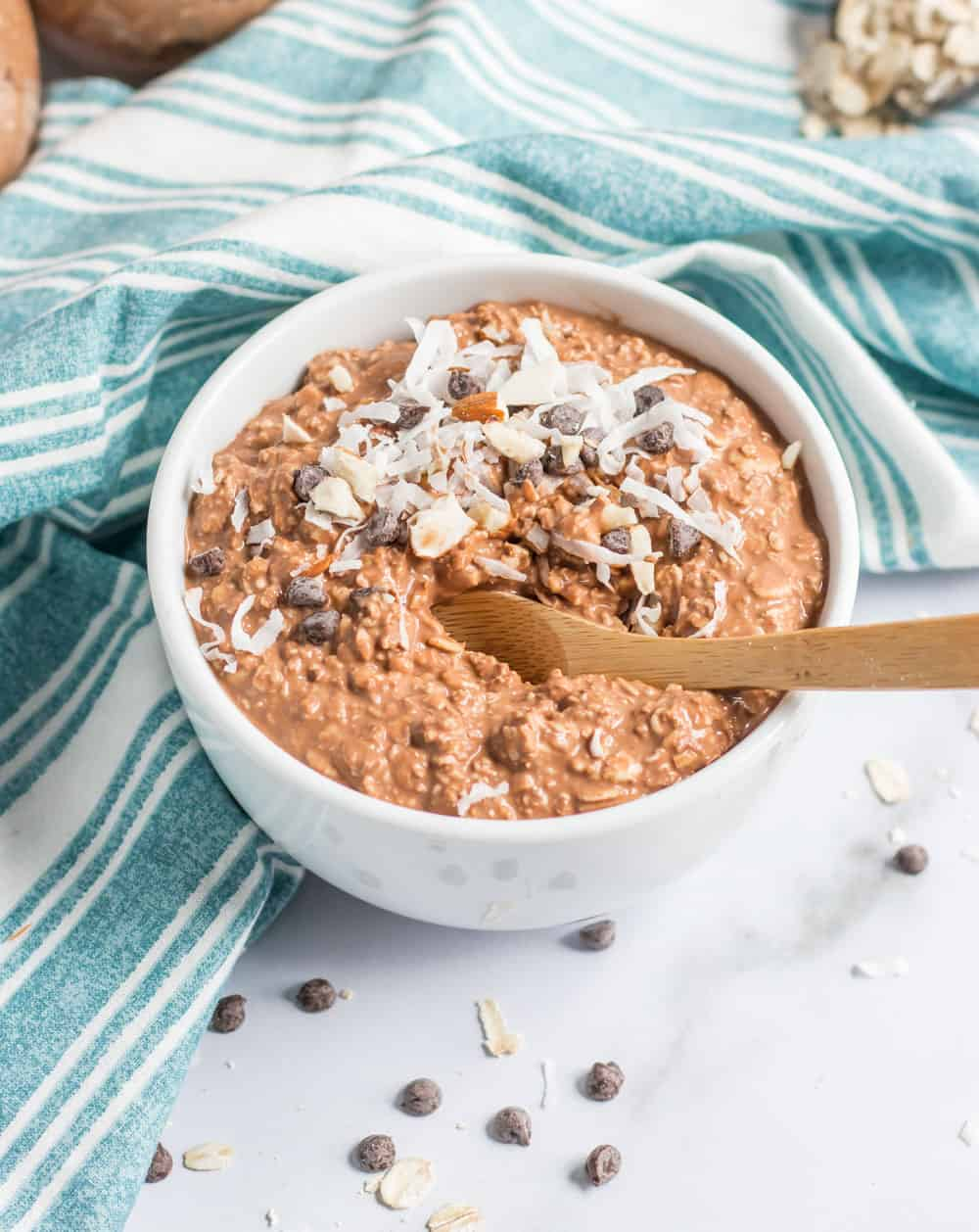Spoon in bowl of oatmeal with chocolate chips.
