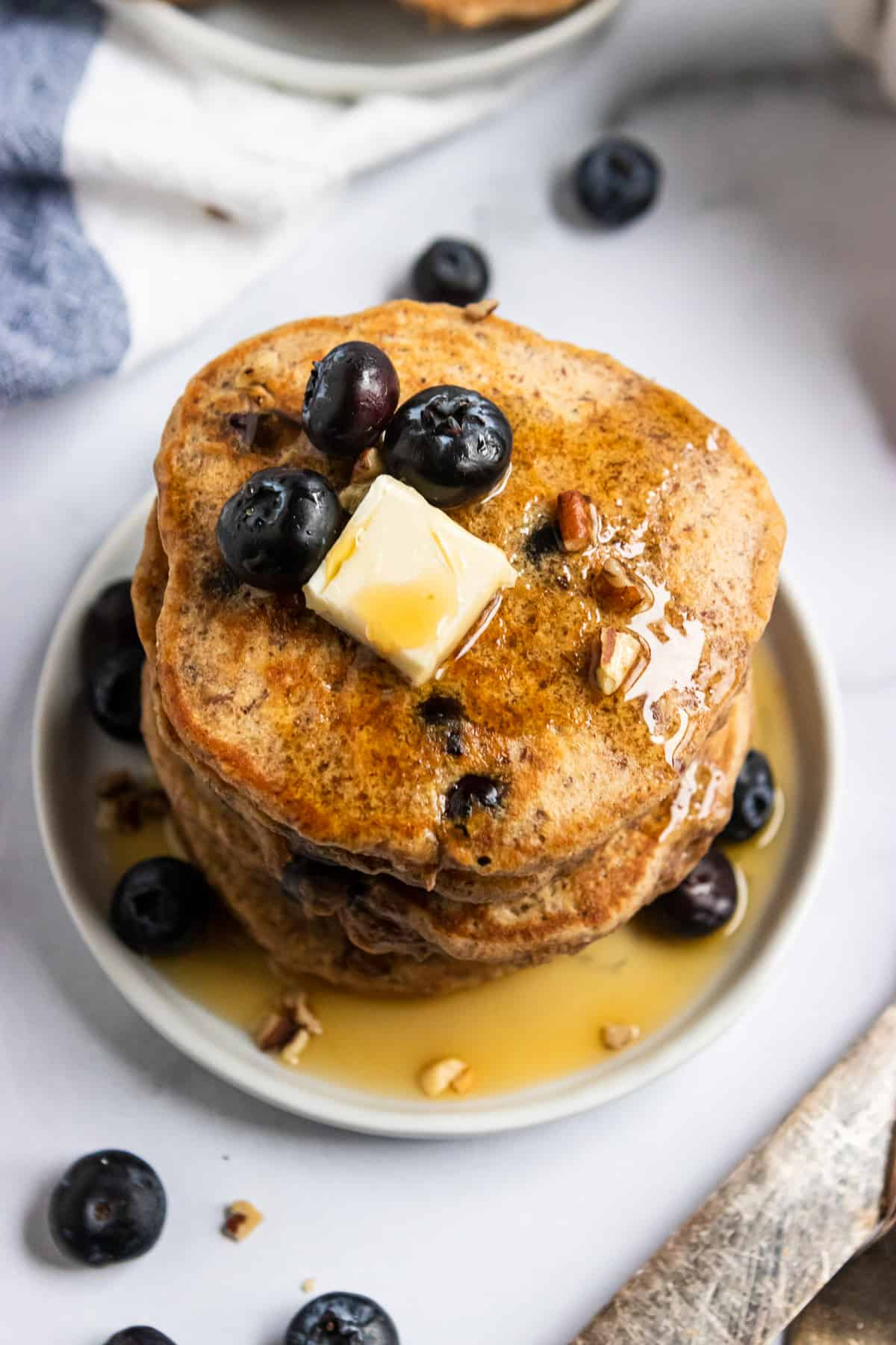 Close up of whole wheat flax pancakes on plate with butter and fresh berries.