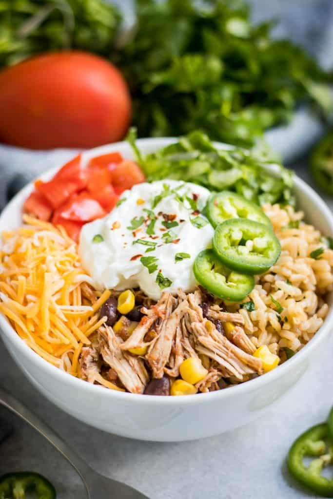 These Simple Slow Cooker Chicken Burrito Bowls are an easy way to bring dinner to the table without all the time and hassle. Juicy shredded chicken, black beans, and the right amount of spice--plus, the topping options are endless!