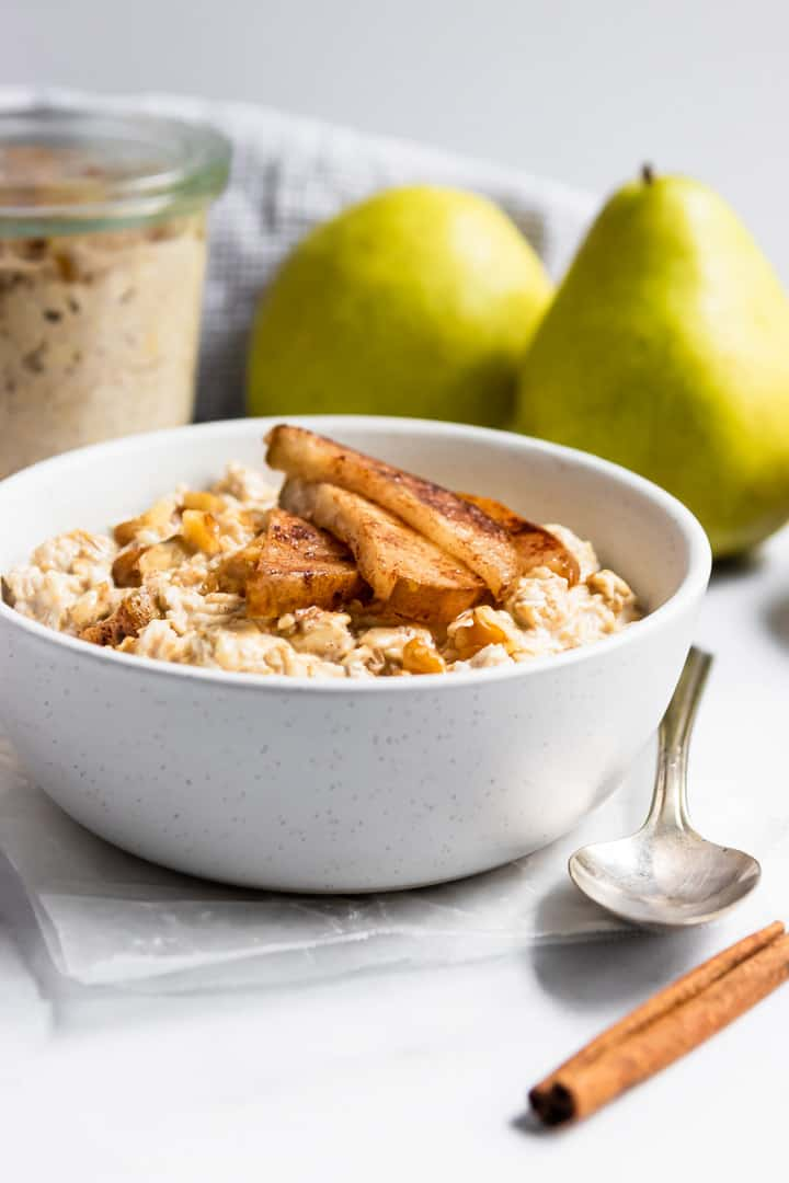 Cinnamon pears on top of oatmeal in white bowl.