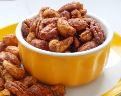 Yellow bowl with maple candied pecans, cashews and almonds.