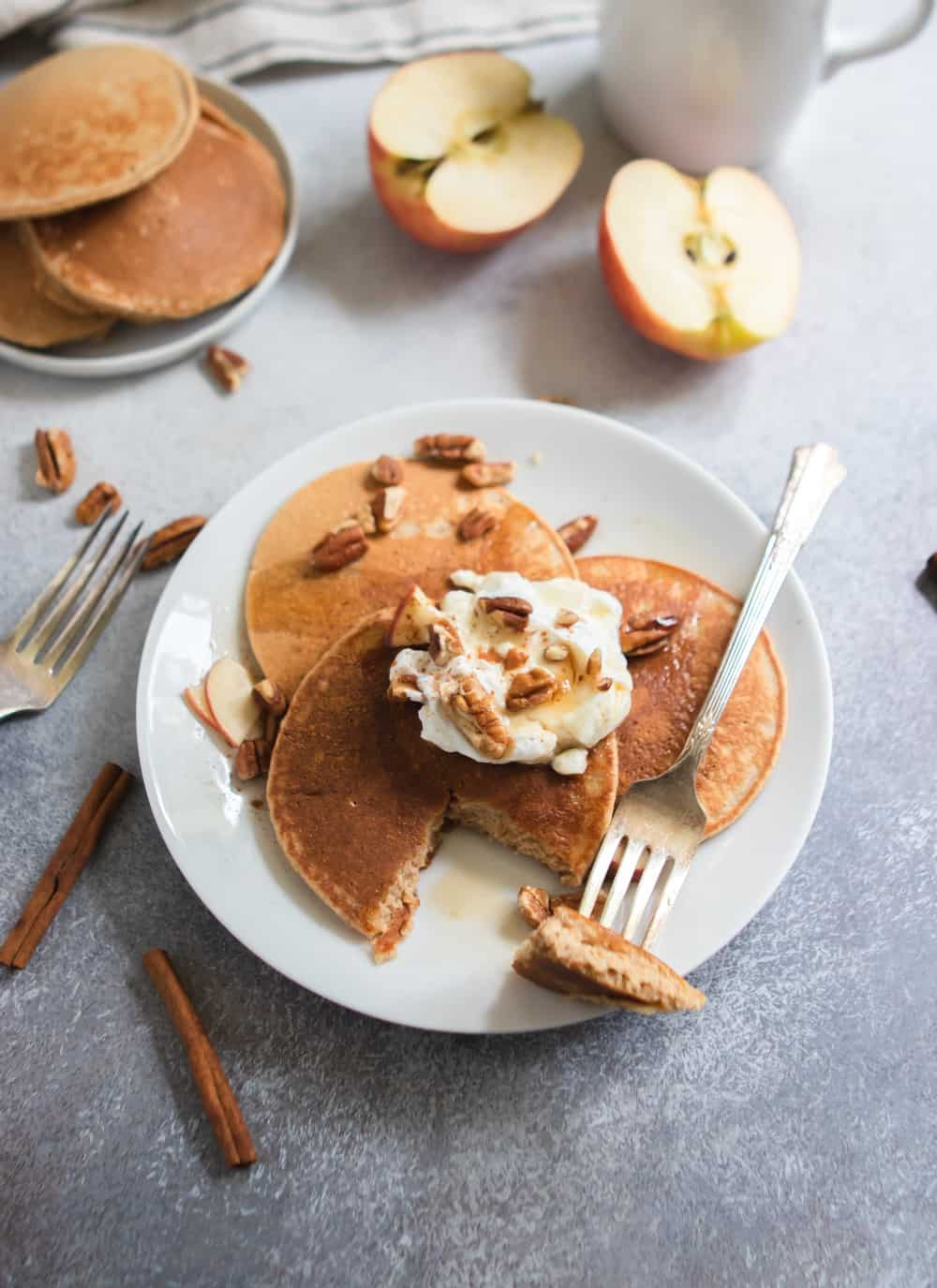 Apple oatmeal pancakes with maple syrup, pecans and yogurt.
