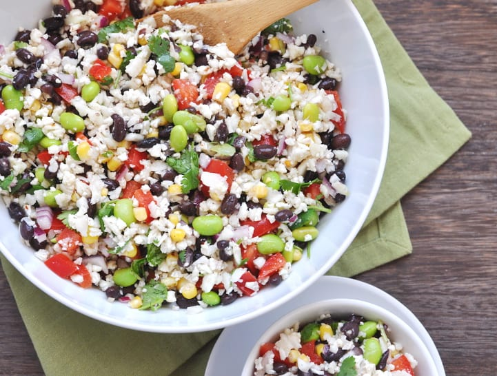 Bowl of cauliflower rice salad with black beans, peppers, corn and more in white bowl with spoon.