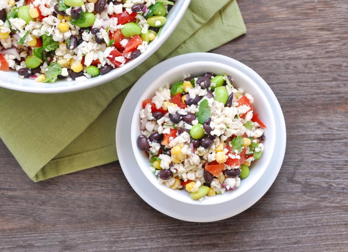 White bowl of cauliflower rice salad with green napkin.