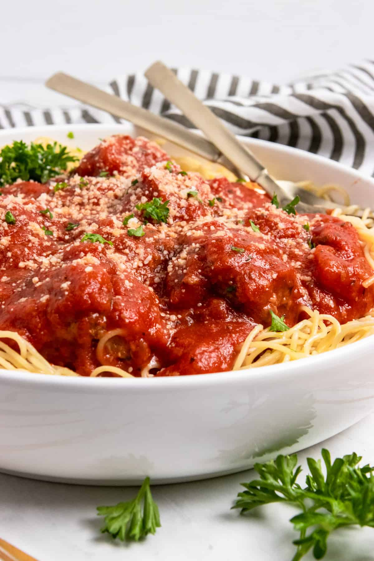 Bowl of pasta with meatballs with zucchini and marinara and parmesan.