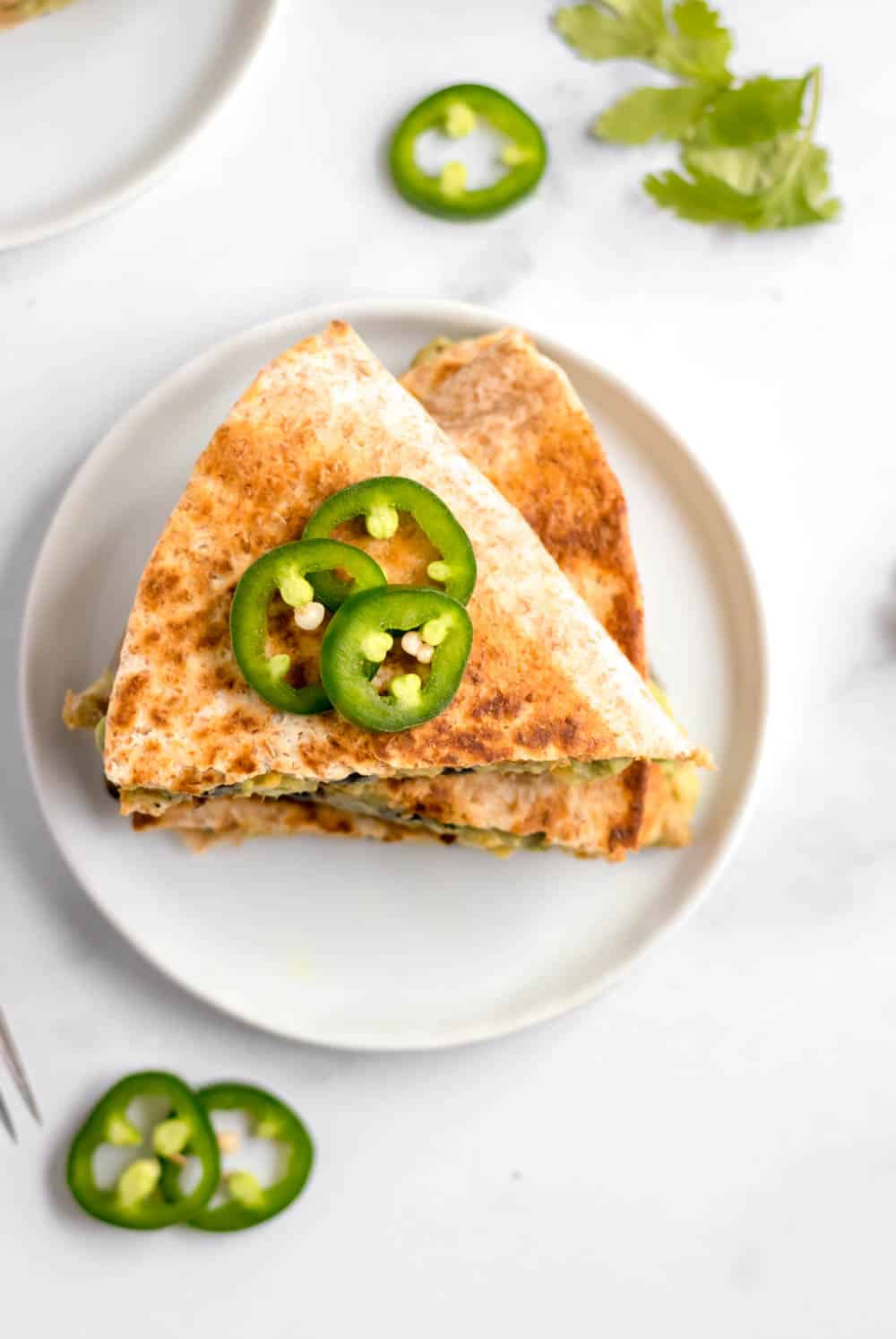Black bean and avocado quesadilla on white plate with jalapeno.