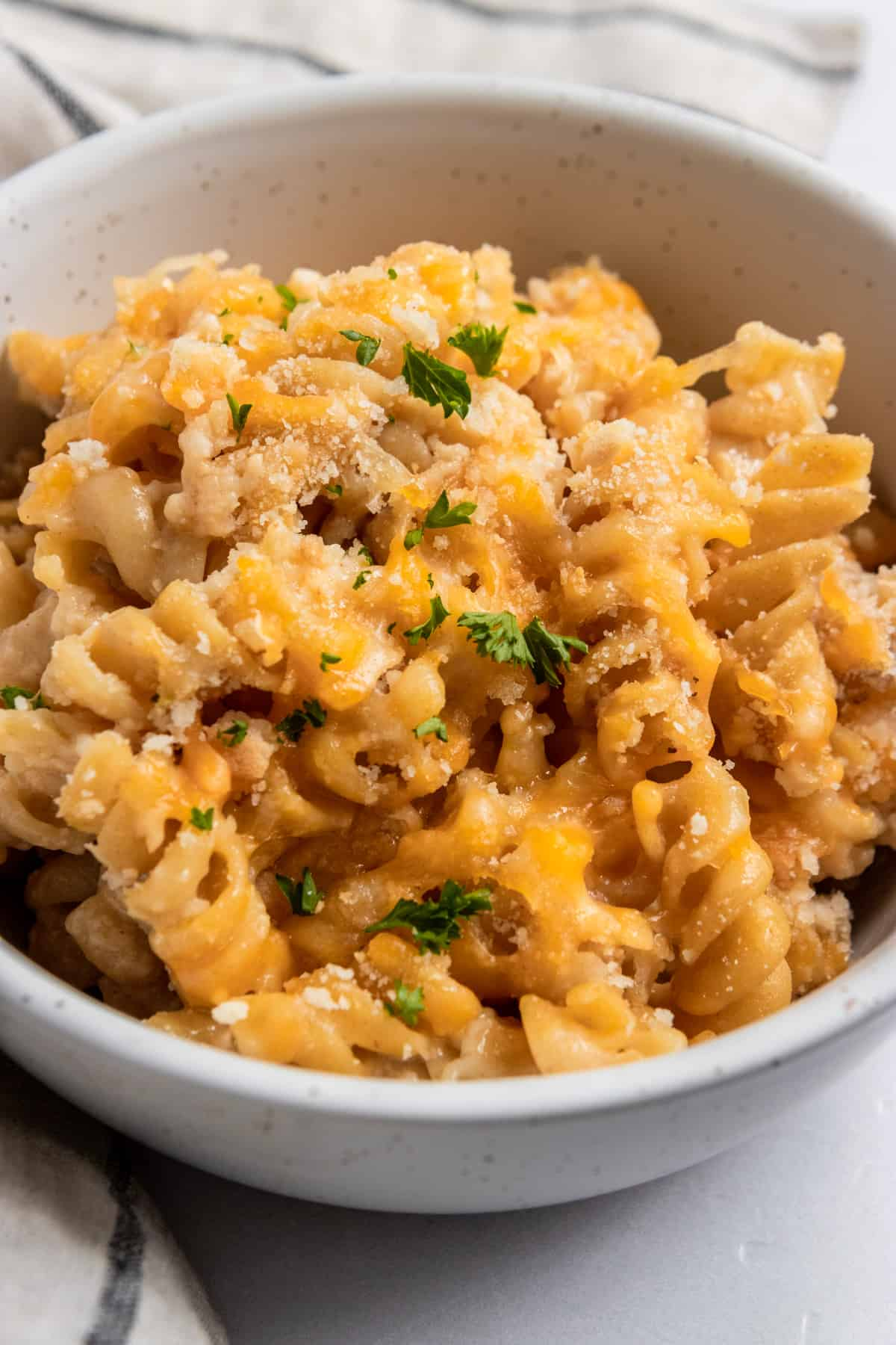 Bowl of macaroni and cheese with breadcrumbs and parsley.