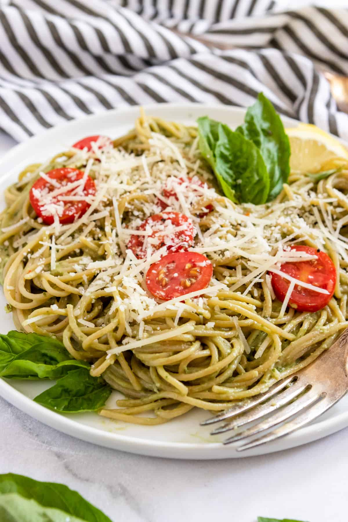 Avocado pesto pasta on white plate with fresh basil and tomatoes.