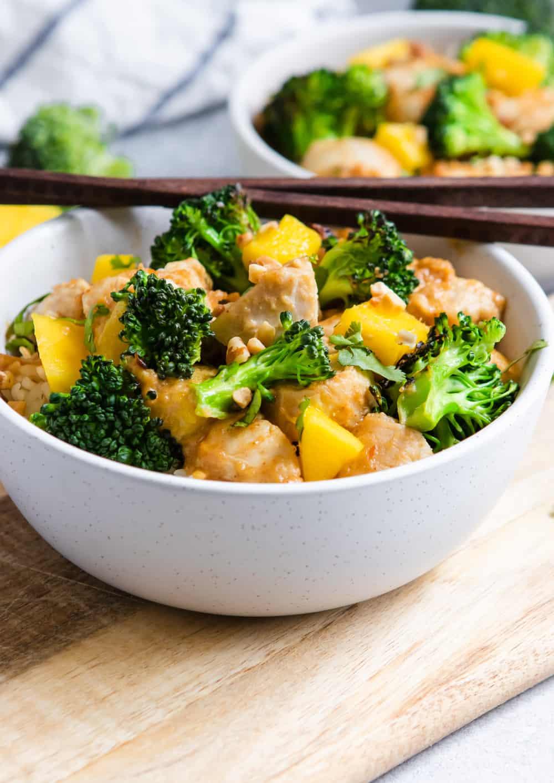Peanut Mango Chicken and Broccoli Stir Fry in bowl with chopsticks.