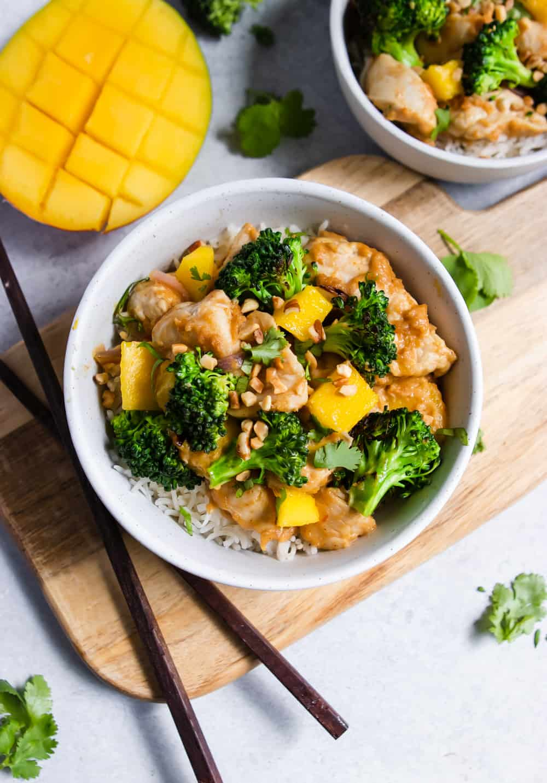 Bowl of chicken stir fry with fresh mango next to it.