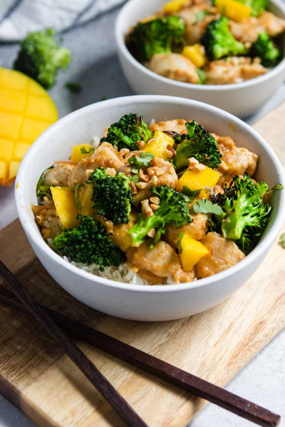 Bowl of stir fry with broccoli, mango and chicken.