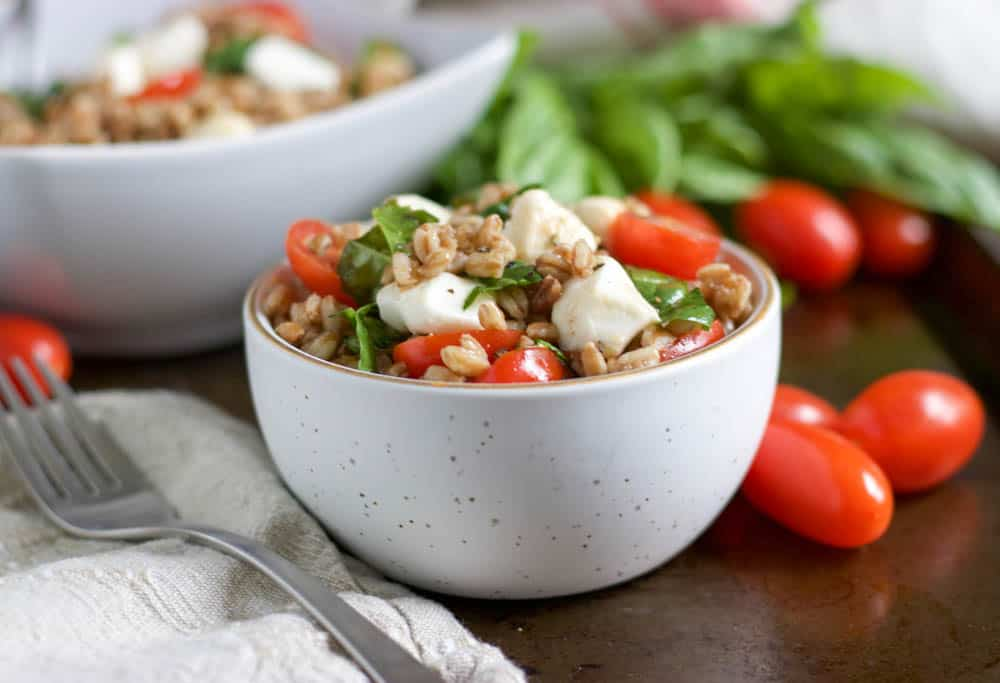 Caprese Farro salad in bowl with tomatoes and basil.