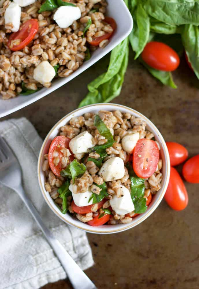 Overhead shot of Caprese Farro Salad with serving dish beside.