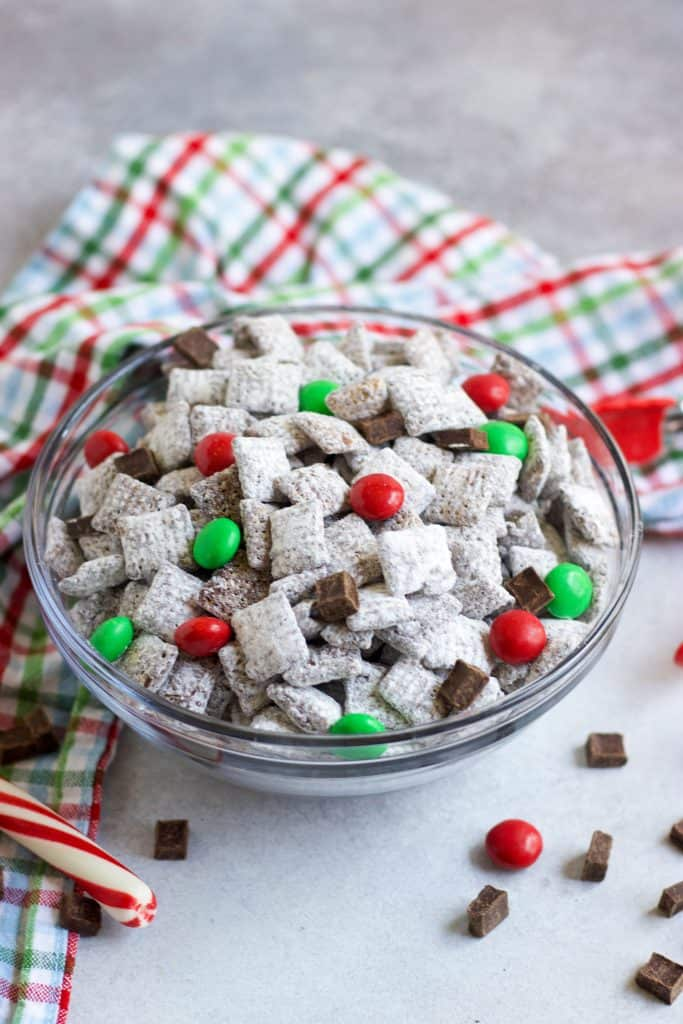 Bowl of peppermint chocolate puppy chow with holiday candies.
