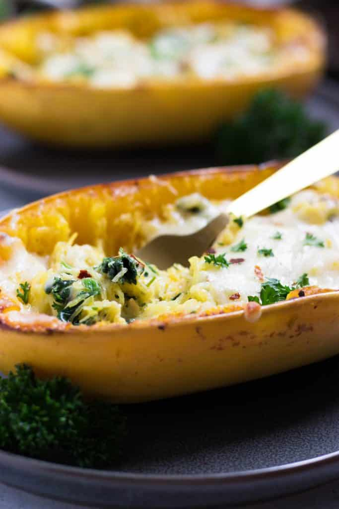 Creamy Pesto + Spinach Stuffed Spaghetti Squash. Creamy, cheesy and packed with veggie goodness. This spaghetti squash dinner will have everyone back for more. #dinner #spaghettisquash #pesto