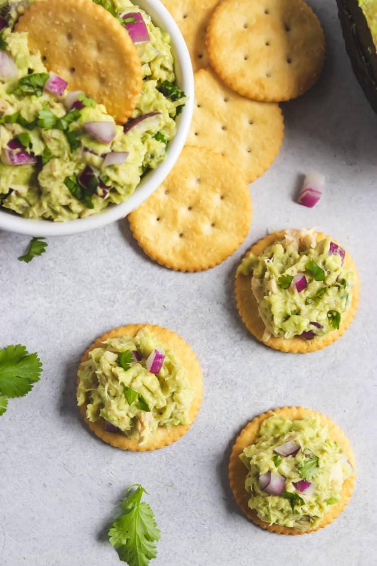 Avocado tuna salad on crackers with onion and cilantro