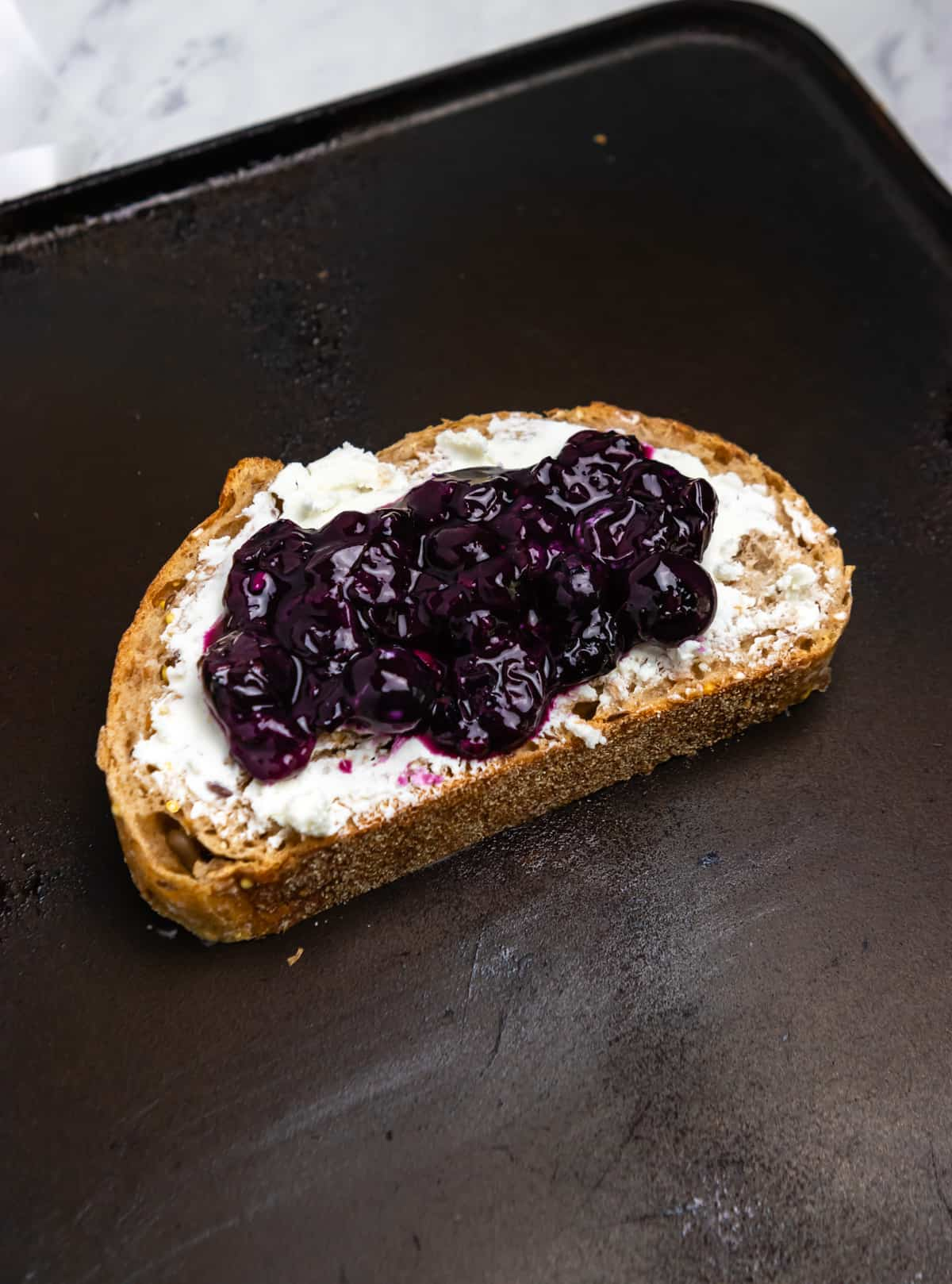Goat cheese and blueberry sauce on bread on skillet.