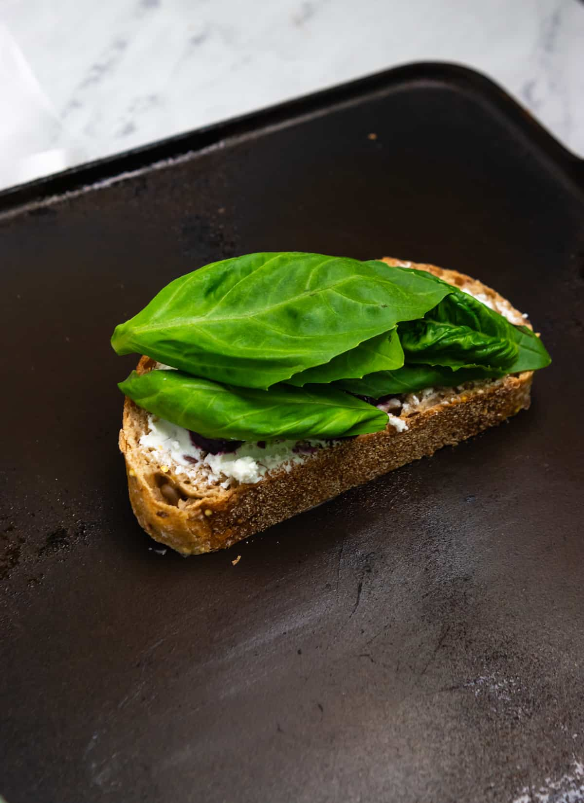 Basil on grilled cheese sandwich on skillet.