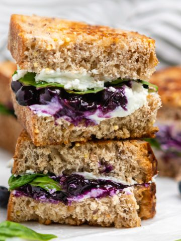 Stacked grilled goat cheese sandwich on counter with blueberries and basil.