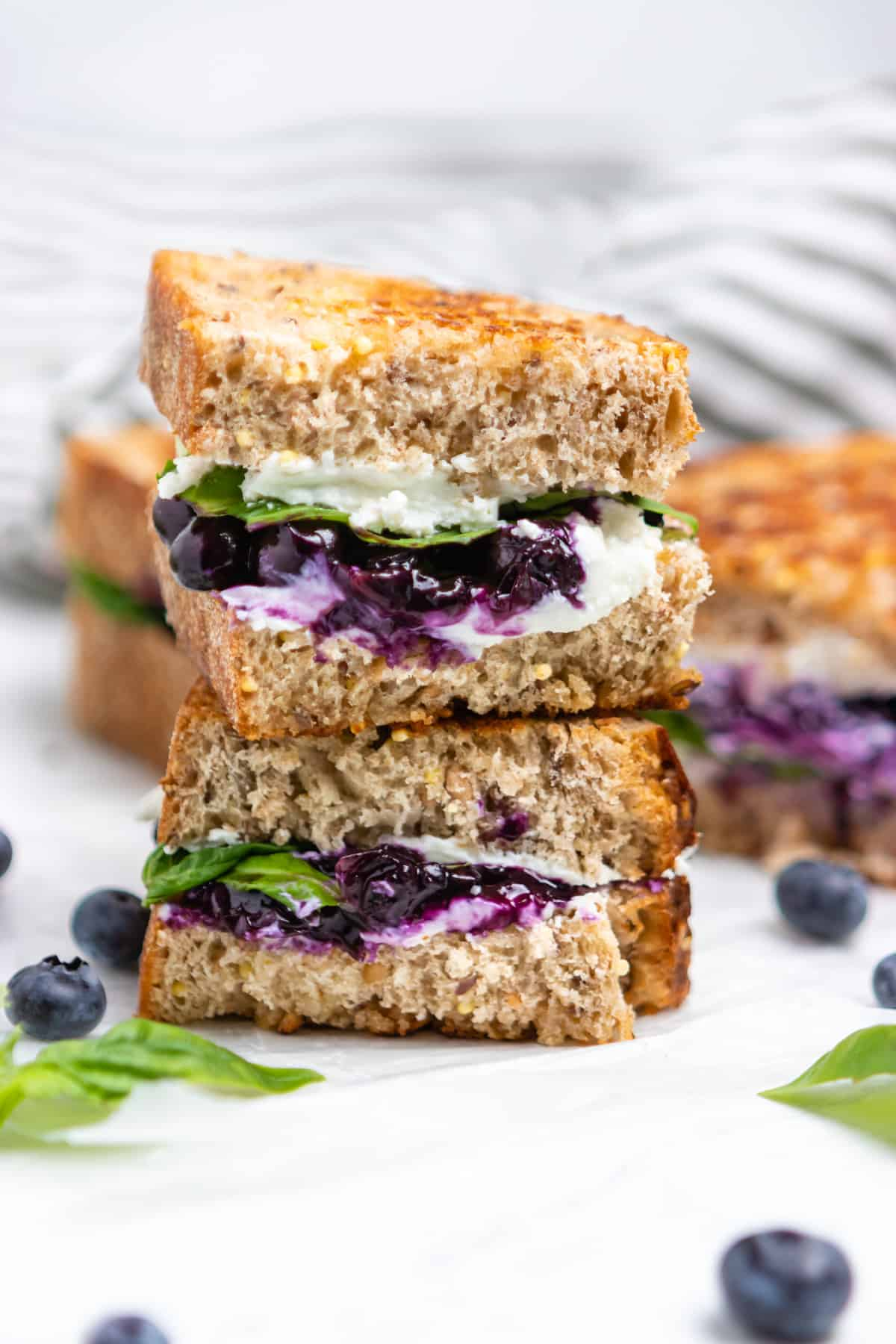 Grilled cheese with goat cheese, blueberries and basil stacked.