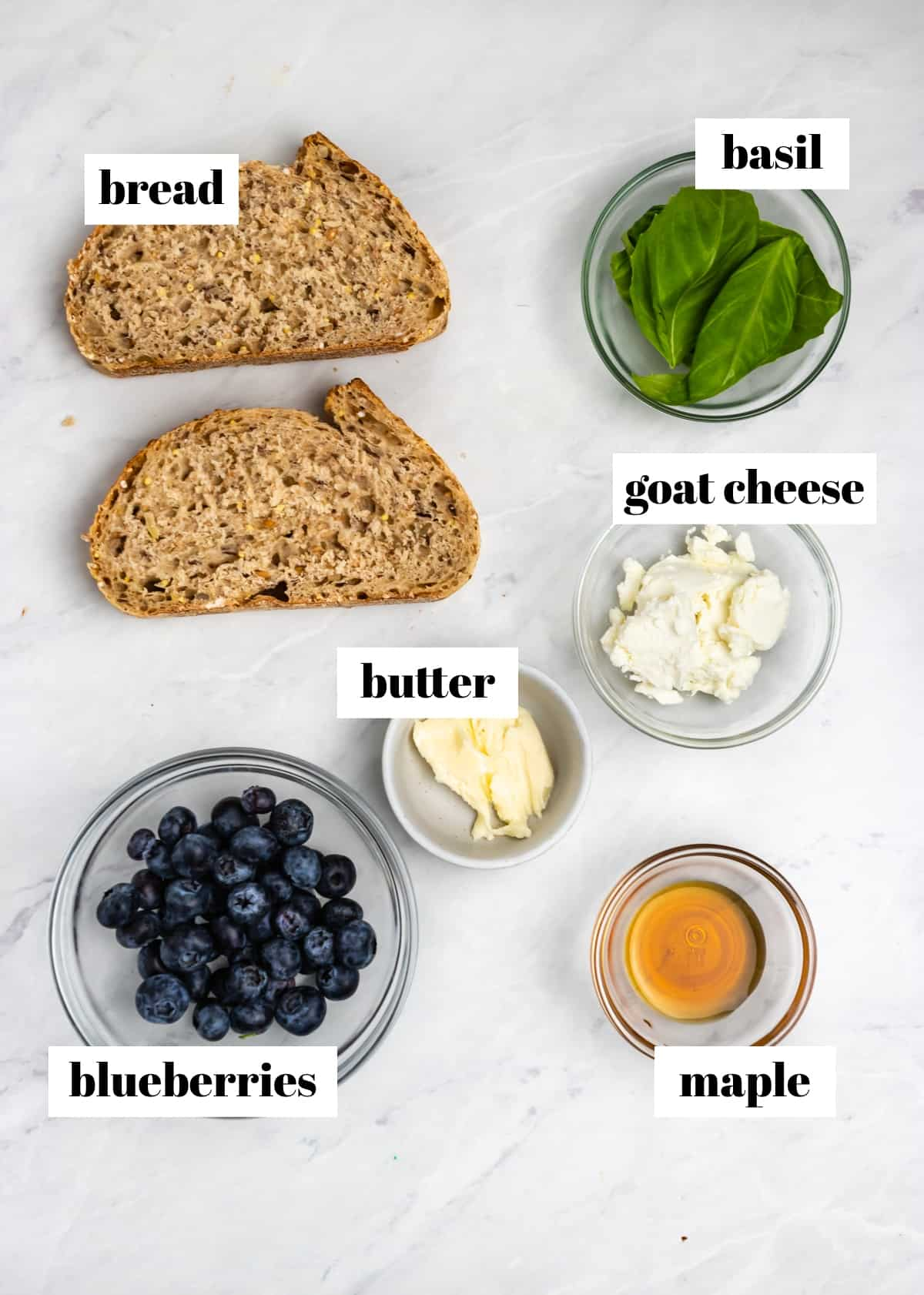 Bread, cheese, basil, blueberries and other ingredients labeled on counter.