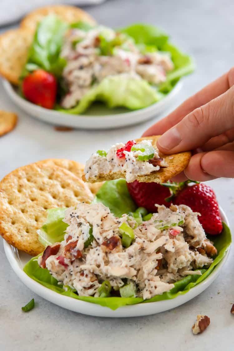 Cracker scooping rotisserie chicken salad on bed of lettuce.
