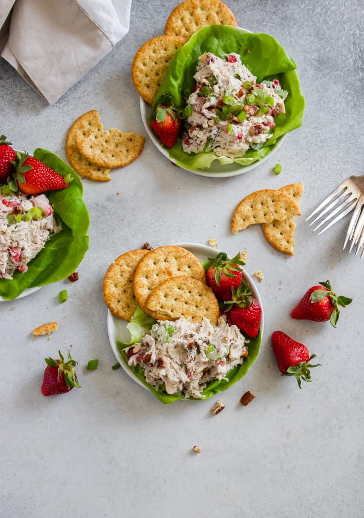 Chicken salad on white plate with berries and crackers.