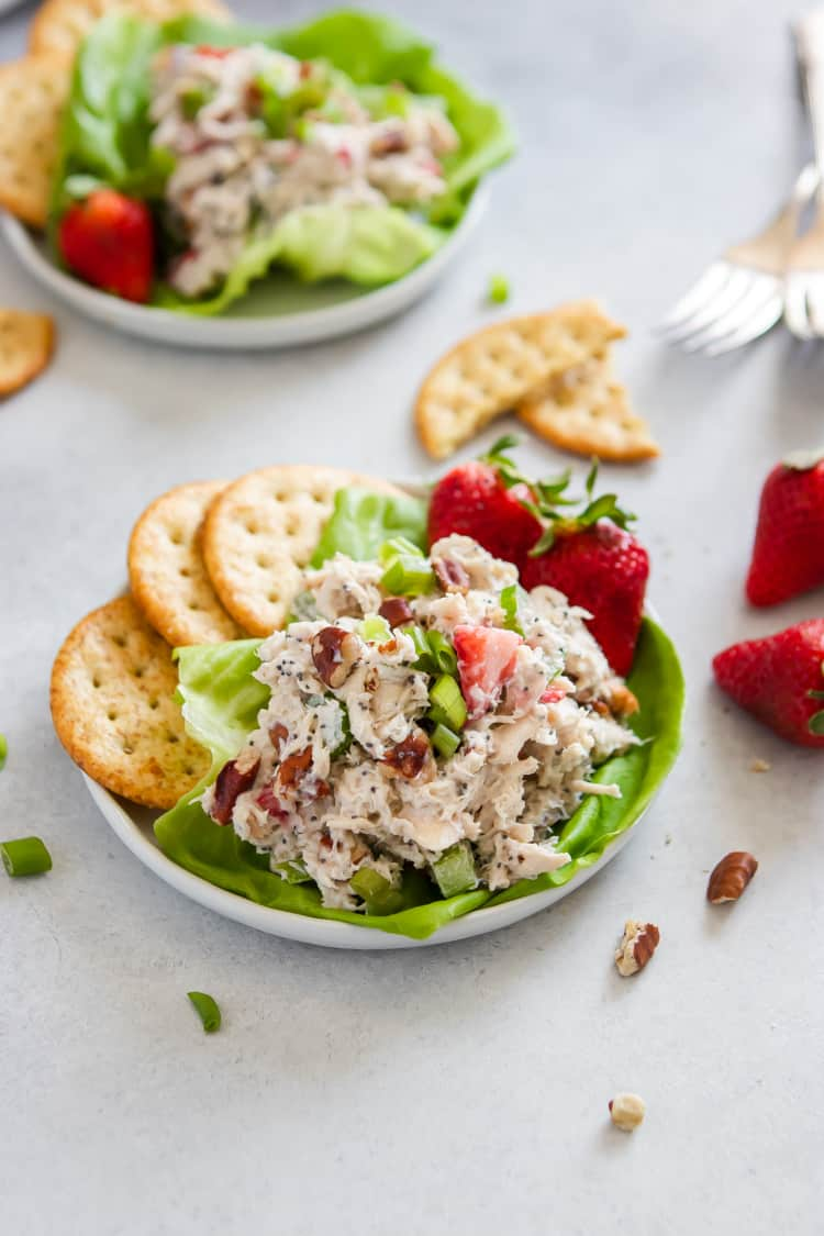 Rotisserie chicken salad on white plate with strawberries and crackers.