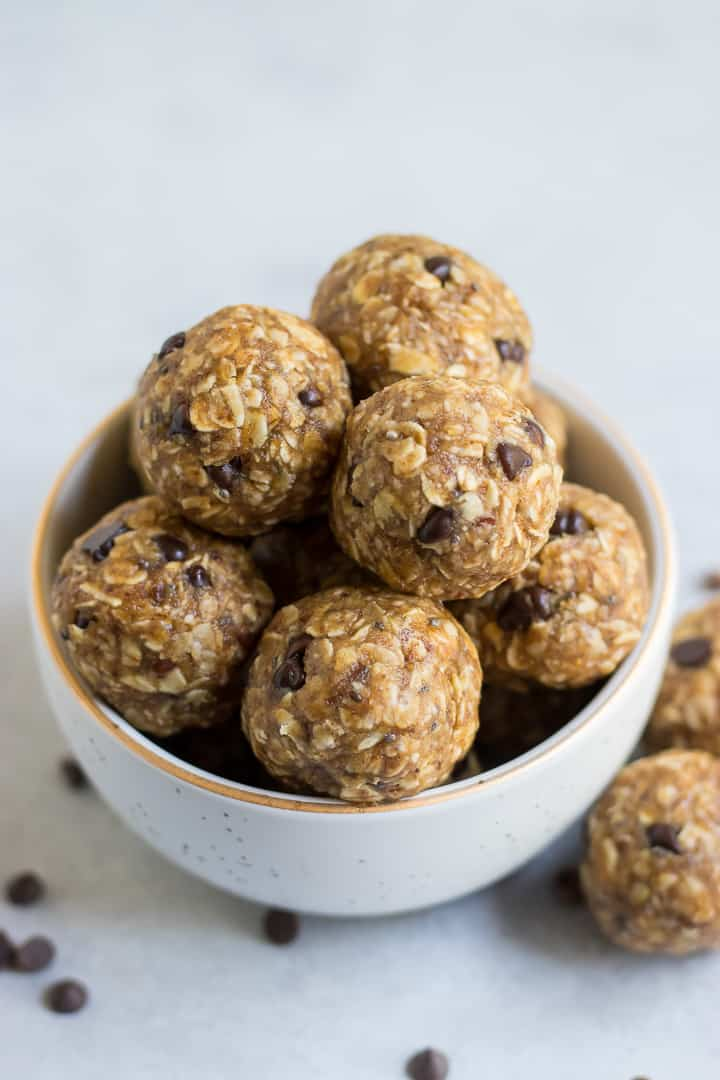 Oatmeal balls with chocolate chips in white bowl with gold trim.