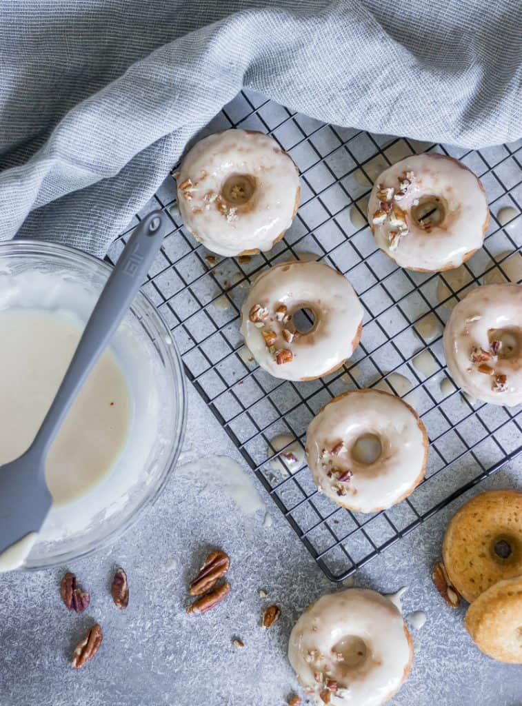 Vanilla glazed donuts on a cooling rack.