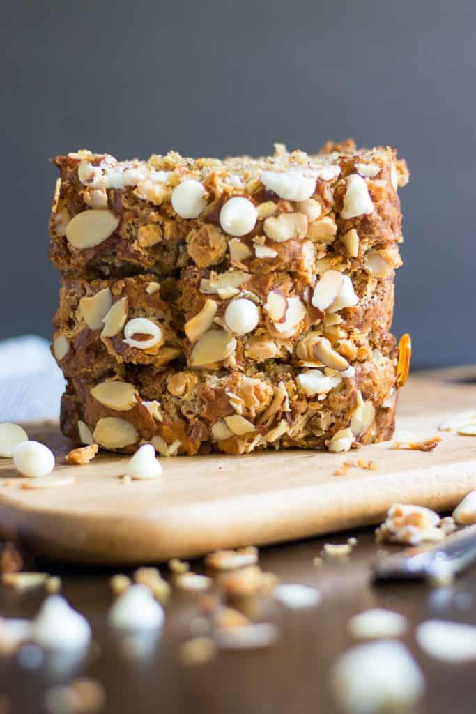 This simple White Chocolate Almond Banana Bread recipe is packed with white chocolate chips, sliced almonds and so rich and moist. Have it for breakfast, a snack or straight from the oven when you are baking! This bread is the BEST! #bananabread #baking #whitechocolate #almond #recipe