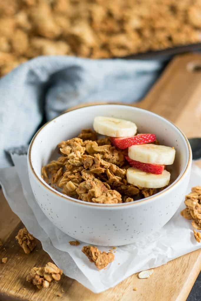 Peanut Butter Granola in bowl with banana and strawberry slices.