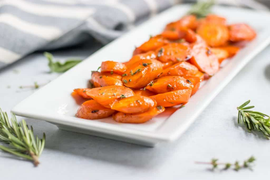 Roasted carrots with fresh herbs on plate.