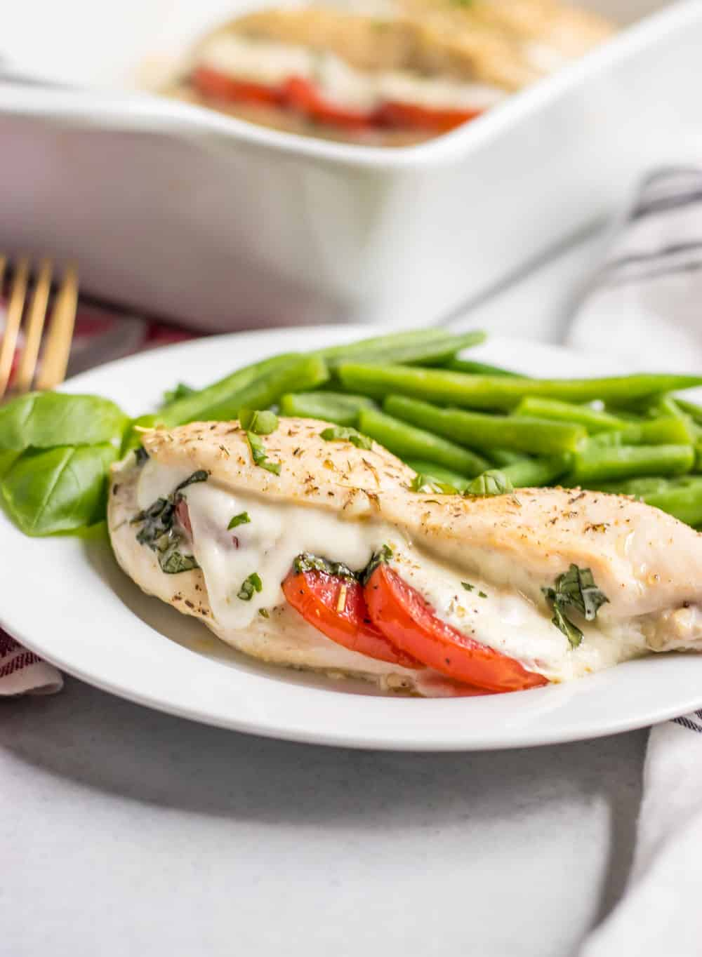 Mozzarella stuffed chicken on plate served with fresh green beans.