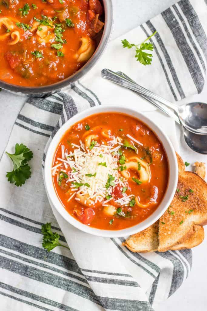 Overhead shot of tomato tortellini soup in white bowl.