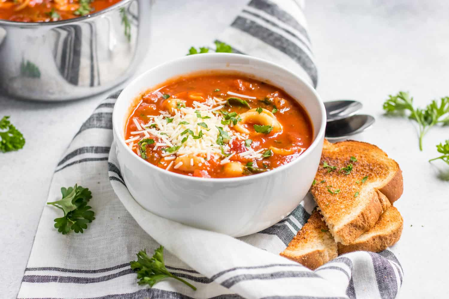 Tomato tortellini soup in bowl with fresh parsley, parmesan and a side of garlic toast.