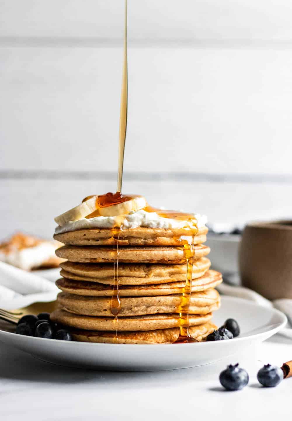 Maple pour shot over stack of banana blender pancakes.
