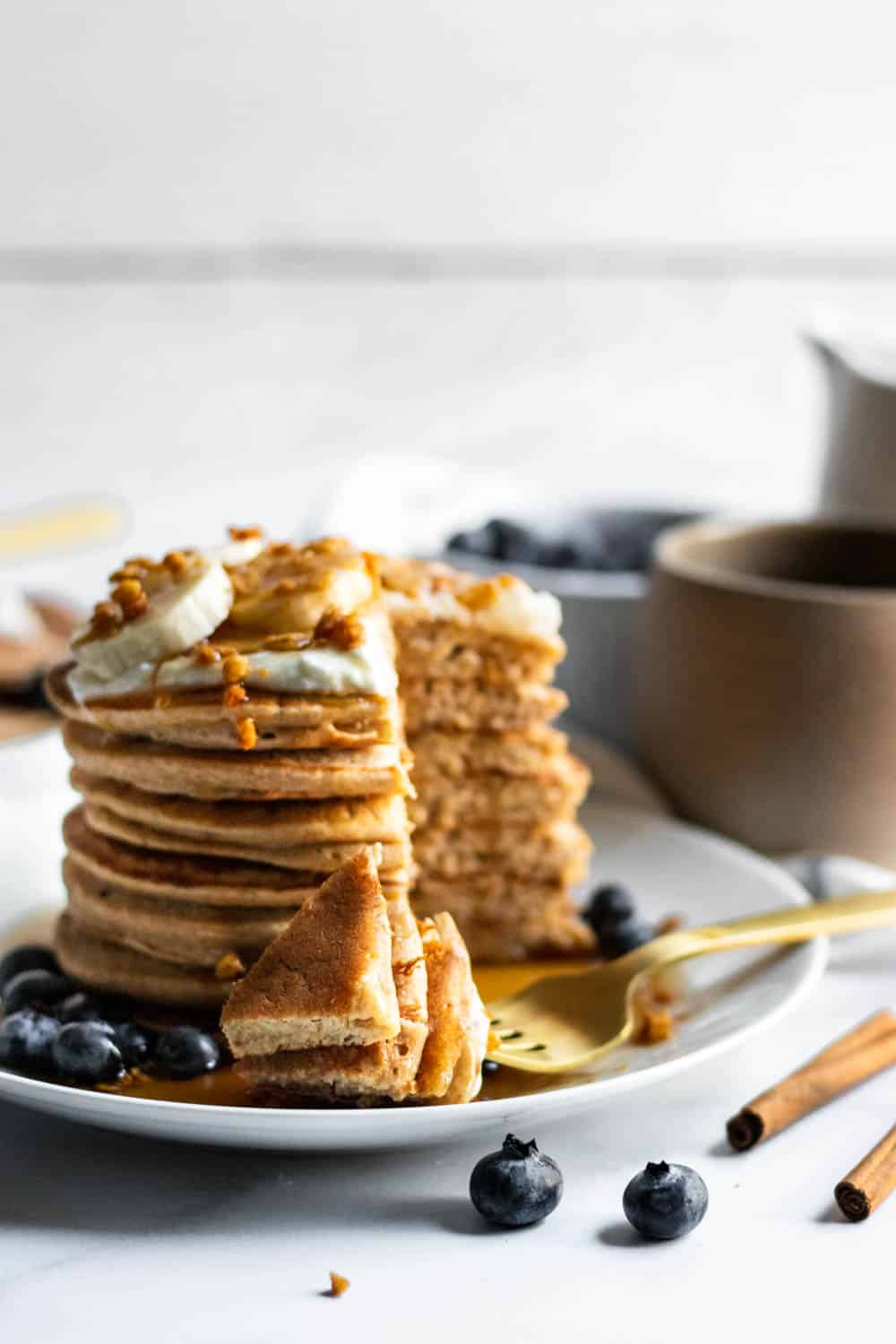 Plate of banana oat blender pancakes stacked with pieces of pancake on a fork.