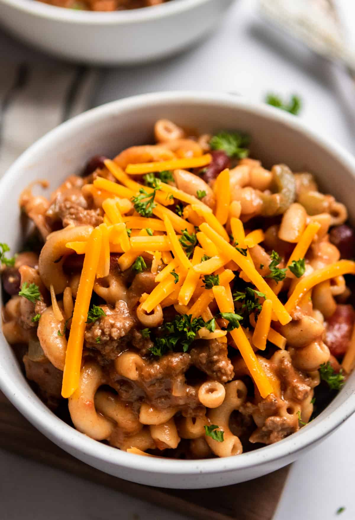 One Pot chili mac and cheese in white bowl with parsley and cheese garnish.