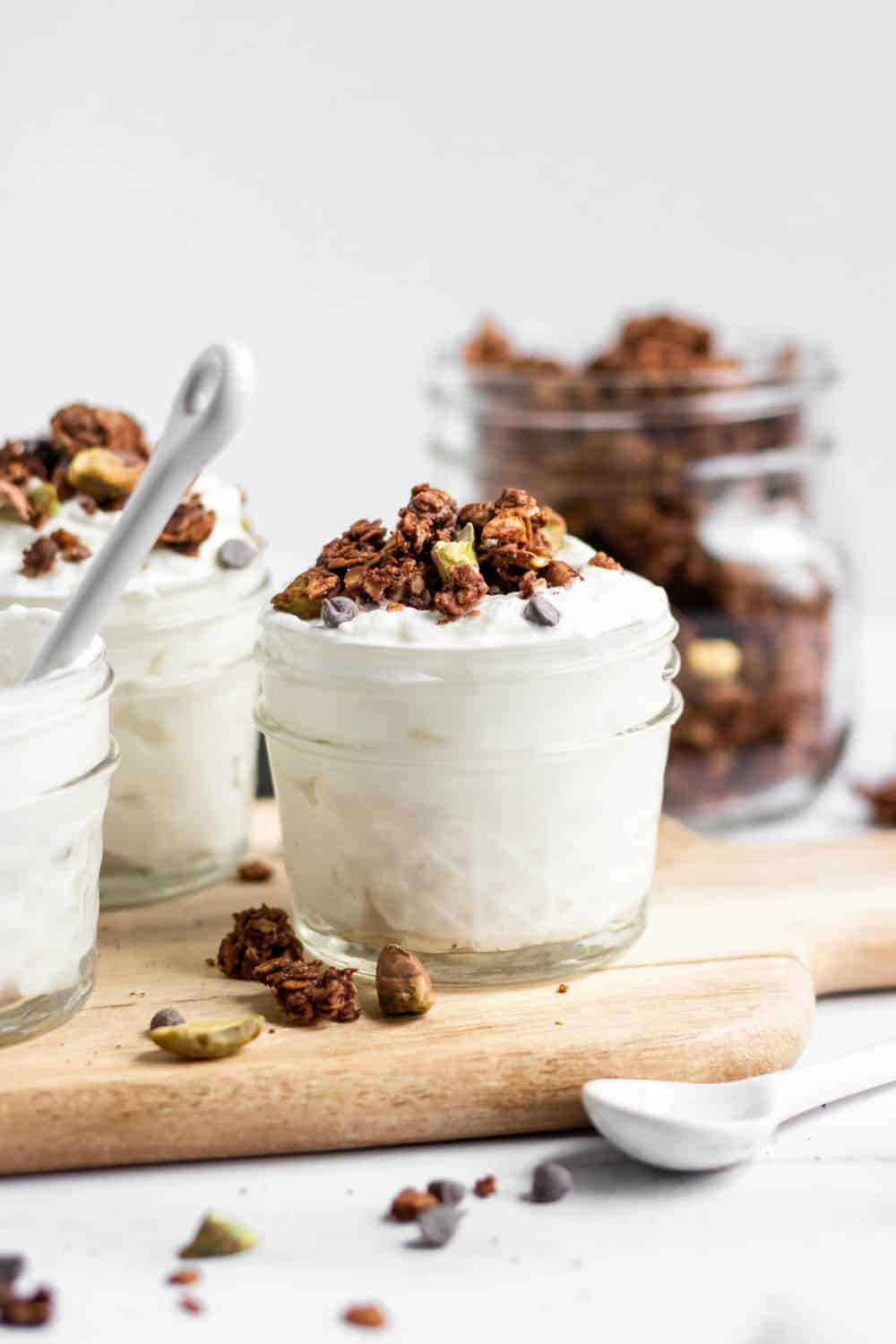 Chocolate Granola in jars over yogurt with pistachios.