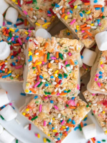 Overhead view of birthday cake rice krispie treats on white plate with sprinkles and marshmallows.