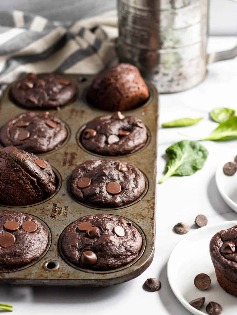 Muffins in muffin tin with flour sifter, spinach and chocolate chips.