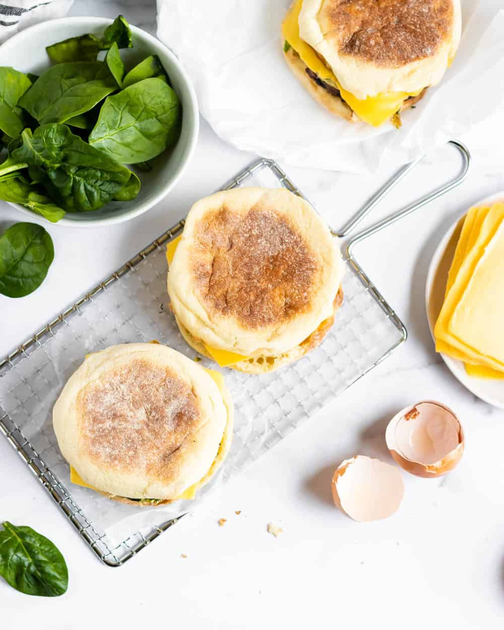 Overhead shot of breakfast sandwiches with ingredients surrounding.