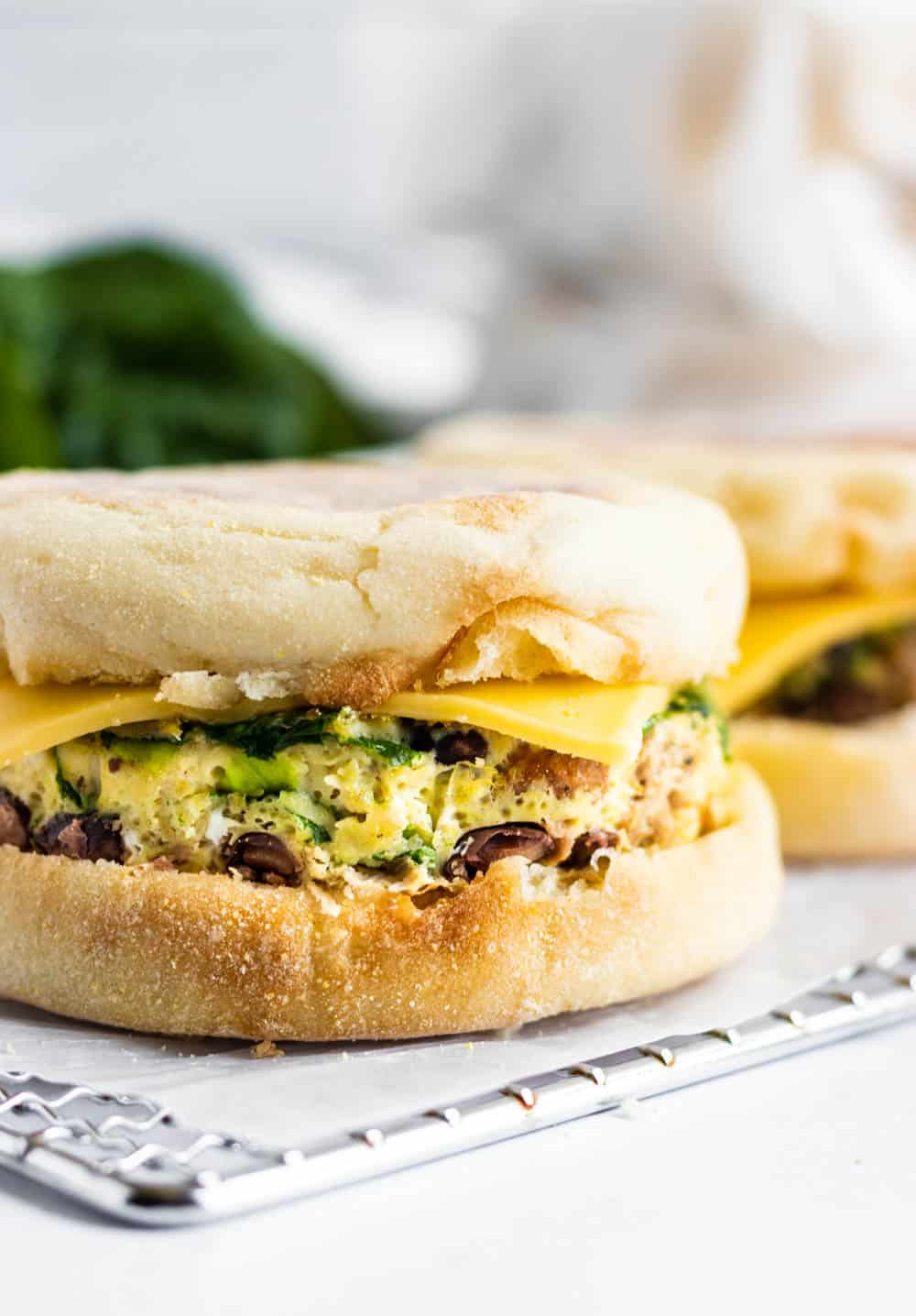 Breakfast sandwich with egg, cheese and black bean on rack.