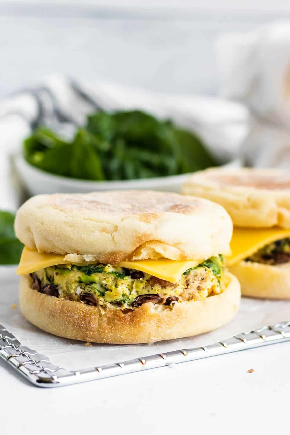 Egg and sausage breakfast sandwich on rack with cheese and spinach.